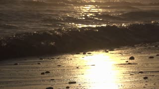 Golden hour sun reflection during sunset on beach slow motion