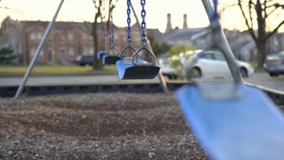 Group of empty swings in abandoned playground 4k