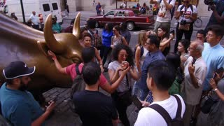 Groups of people posing with Bull in financial district of NYC
