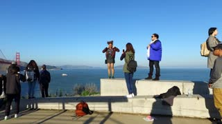 Groups of people taking pictures with Golden Gate Bridge background