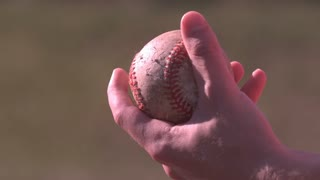 Hand gripping baseball in slow motion