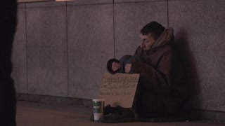 Homeless man sitting in the cold weather of Chicago Illinois 4k