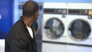 Male standing in laundromat texting on phone 4k
