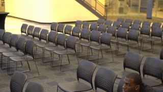 Man alone in crowd of chairs thinking 4k