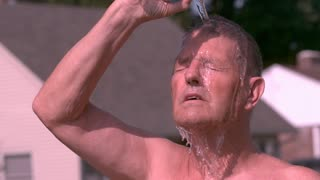 Man pours bottle of water on head in hot summer sun slow motion