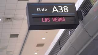 Man walking by Las Vegas departure gate sign at airport 4k