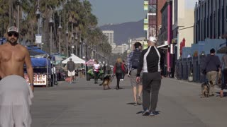 Morning pedestrians walking along Venice Beach store fronts 4k