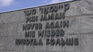 Never Again memorial sign at Dachau camp 4k