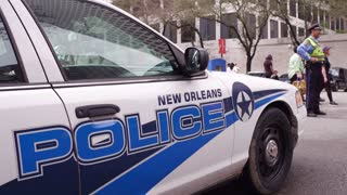 NOLA police vehicles parked on side of street with officer in background 4k