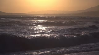 Ocean waves crash into shore slow motion sunset