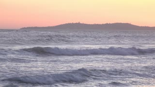 Ocean waves with island in background during sunset 4k