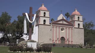 Old Mission Santa Barbara with wooden cross in grass 4k
