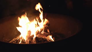 People gathered around fire pit in darkness 4k