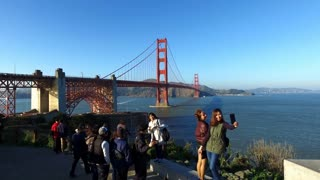 People taking picture with Golden Gate Bridge in background