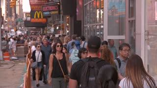 People walking down busy sidewalk of Times Square slow motion