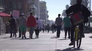 People walking down sidewalk on Venice Beach store fronts 4k