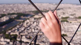 Person holding on to metal fence while overlooking city 4k