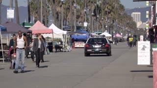 Police cruiser going down sidewalk at Venice Beach California 4k