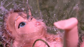 Pouring water on burnt baby dolls face slow motion