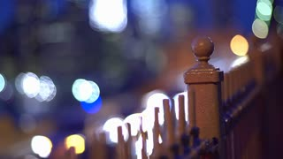 Railing in city with passing by traffic lights in background 4k