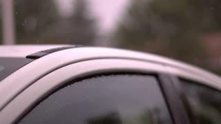 Rain landing on car window slow motion