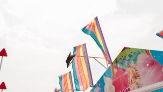 Rainbow flags waving at carnival food stand slow motion
