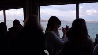 Riders on Staten Island Ferry taking photos of Statue of Liberty 4k