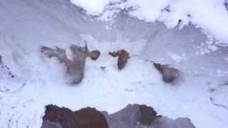 Rotating above frozen waterfall aerial view 4k