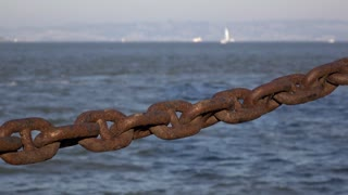 Rusted and aged heavy duty chain along ocean water 4k