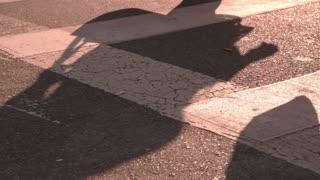 Shadow of pedestrian crossing street slow motion