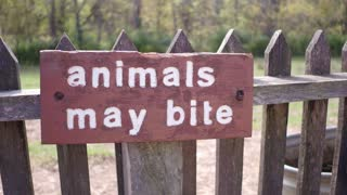 Sign posted for animals that may bite on farm 4k