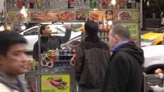 Smiling street vendor serving customers food in New York 4k