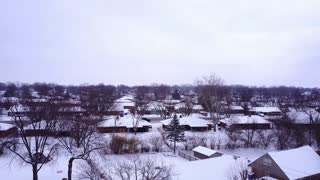 Snow covered suburban neighborhood with street traffic aerial view 4k