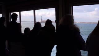 Statue of Liberty seen from Staten Island Ferry with passengers aboard 4k