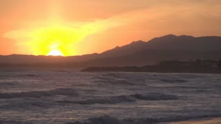Sunset behind mountains with ocean waves