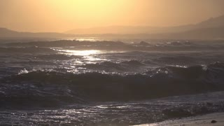Sunset with ocean waves coming towards shore slow motion