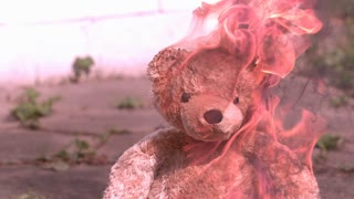 Teddy bear on fire with large flames slow motion