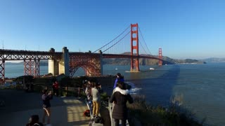 Tourists taking photos with Golden Gate Bridge in background