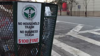 Trash can with sign on corner of NYC intersection 4k