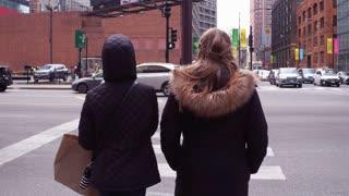 Two female pedestrians crossing sidewalk in downtown Chicago 4k