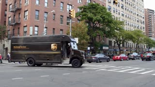 UPS truck driving through downtown NYC intersection 4k
