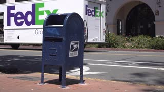 USPS mailbox with Fedex delivery truck in background 4k