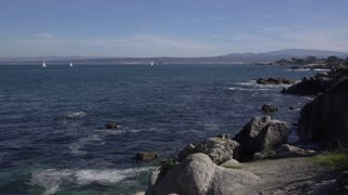 Vast ocean with sailboats in distance and rocks along coast 4k