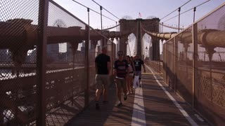 Walking across Brooklyn Bridge with other tourists