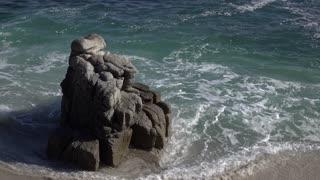 Water from ocean surrounding rock on shore 4k