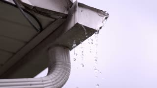 Water overflowing from rain gutter in slow motion
