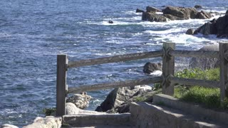Wooden railing along ocean rocks 4k