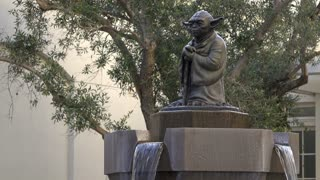 Yoda water fountain flowing on peaceful afternoon 4k