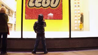 Young child standing in front of Lego store in New York 4k