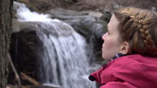 Young female in nature with waterfall background 4k